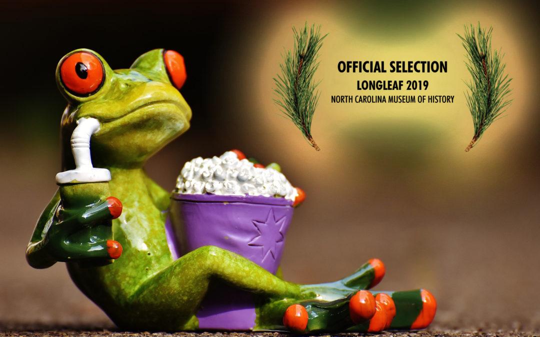 Image of a Frog eating Popcorn with Longleaf Film Festival Laurels